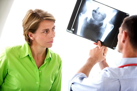Stock Photo: 4269-1199 Doctor examining X-ray of hip prosthesis of a 50 years old patient