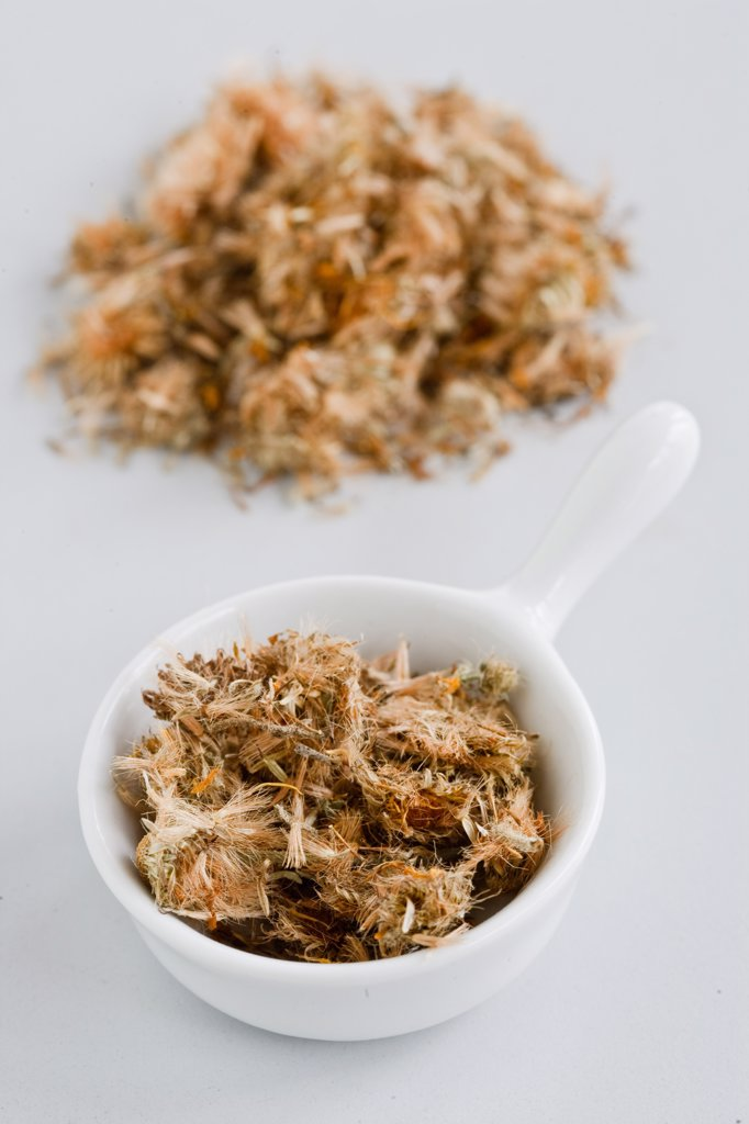 Dried blossoms of the arnica plant (Arnica montana), for use in herbal medicine. The blossoms are prepared as a tincture (spirit solution) or infusion and used as a natural remedy against bruising and to reduce inflammation. : Stock Photo