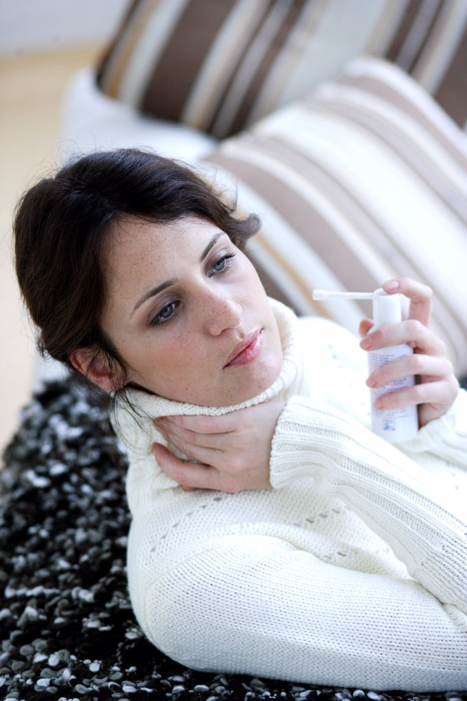 Woman using collutory spray for sorethroat. : Stock Photo
