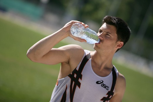 Stock Photo: 4269-1281 Sportman still mineral water to rehydrate himself after exercising.