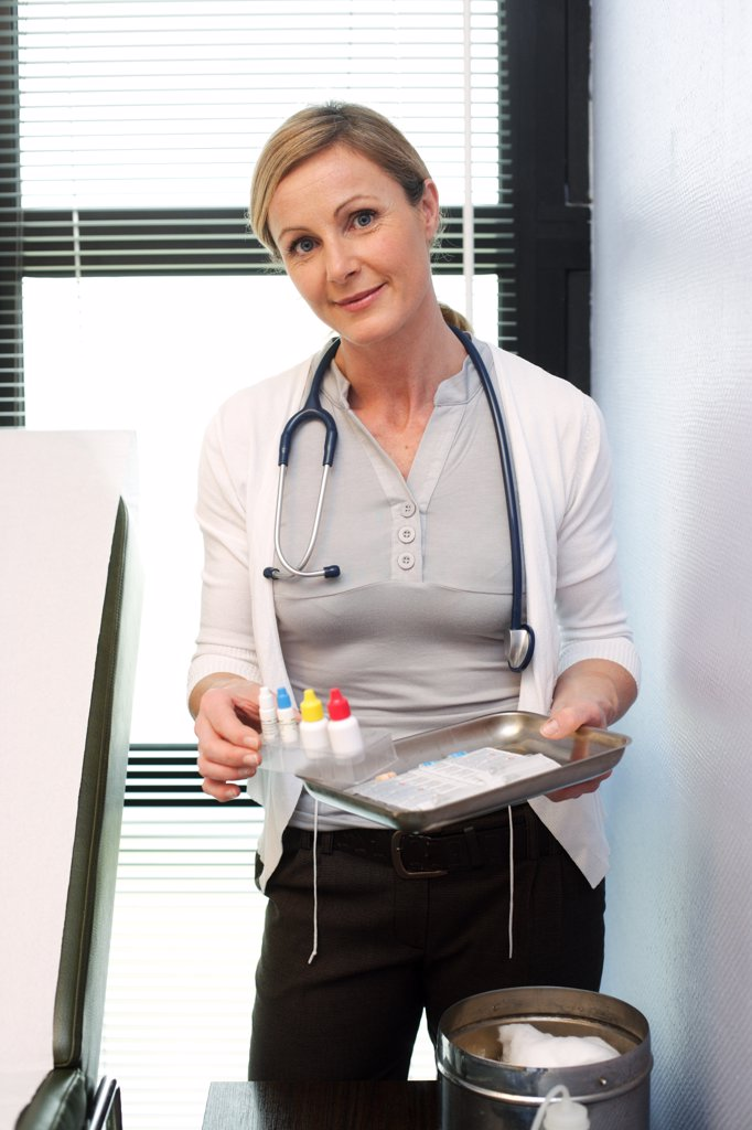 General practitioner tidying up the consulting room. : Stock Photo