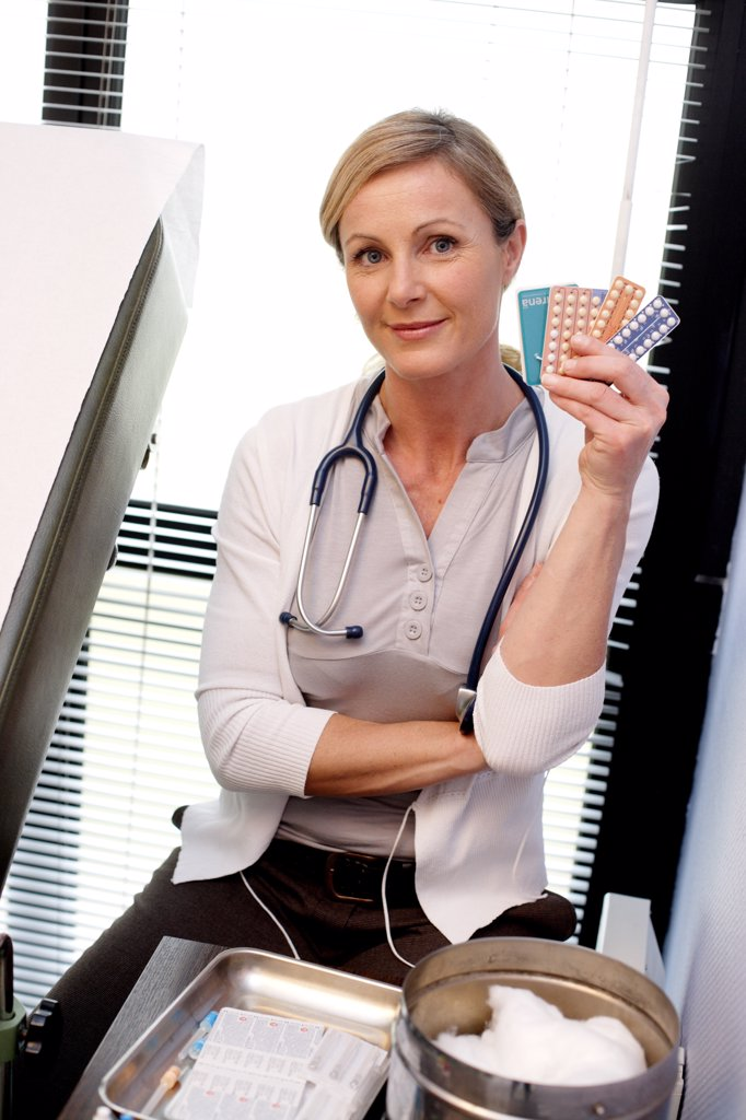 Doctor with various contraceptives. : Stock Photo