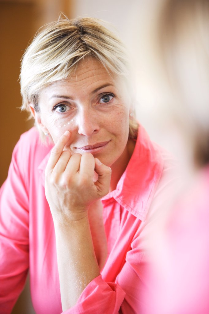50 years old woman applying antiwrinkle cream on her face. : Stock Photo