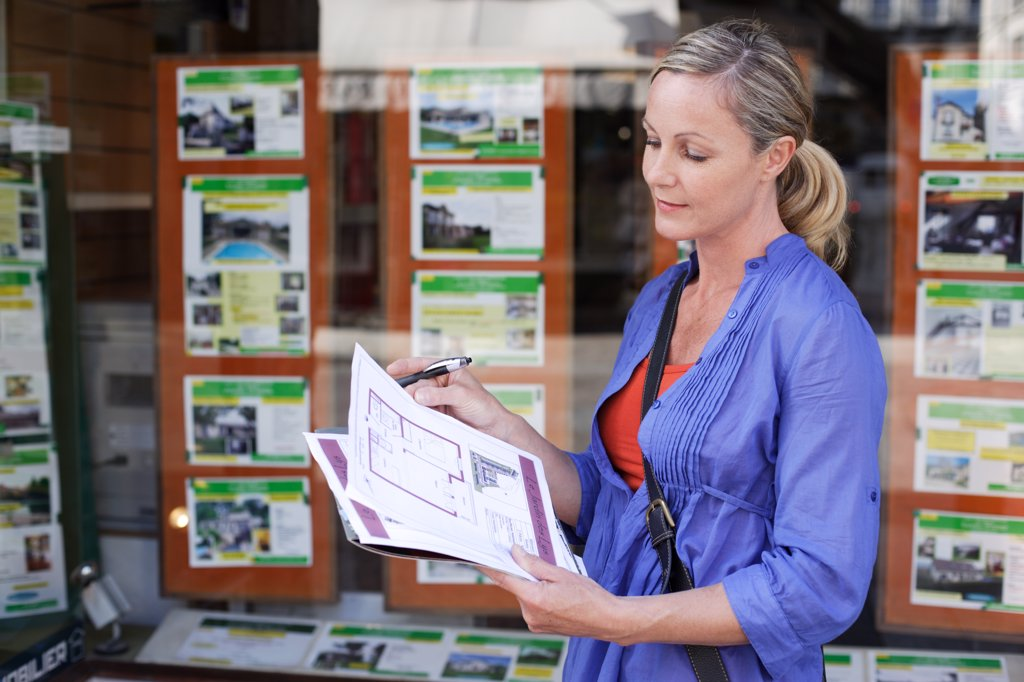 Stock Photo: 4269-14863 Woman looking for ads in a real estate agency.