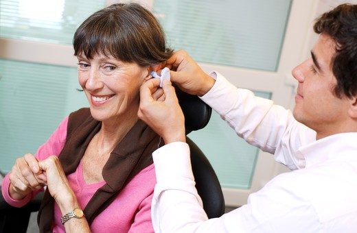 Stock Photo: 4269-15449 Hearing aid specialist making an impression of the auditory canal and eardrum of the patient before making the hearing aid.