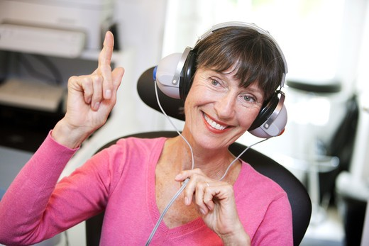 Woman undergoing pure-tone audiometry test and hearing threshold measurement. : Stock Photo