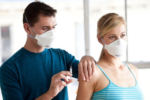 Stock Photo: 4269-15840 Woman receiving vaccination. General practitioner and patient wearing a respiratory protection mask during consultation with contagion hazard.