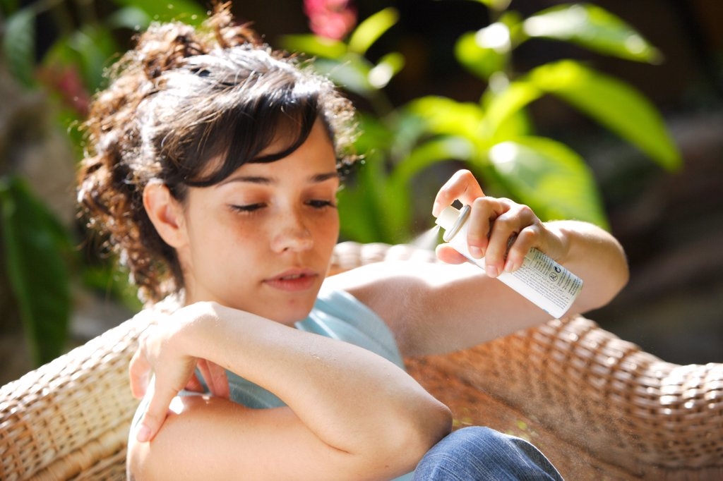 Stock Photo: 4269-1611 Young woman applying spray against insect bites and itching on her arm.