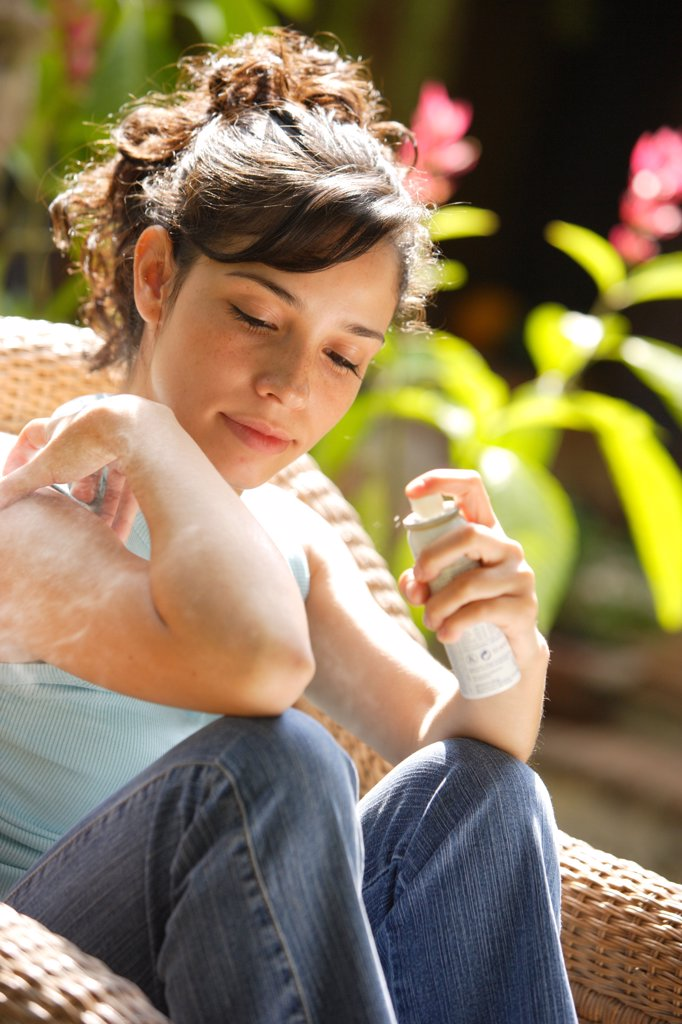 Young woman applying spray against insect bites and itching on her arm. : Stock Photo