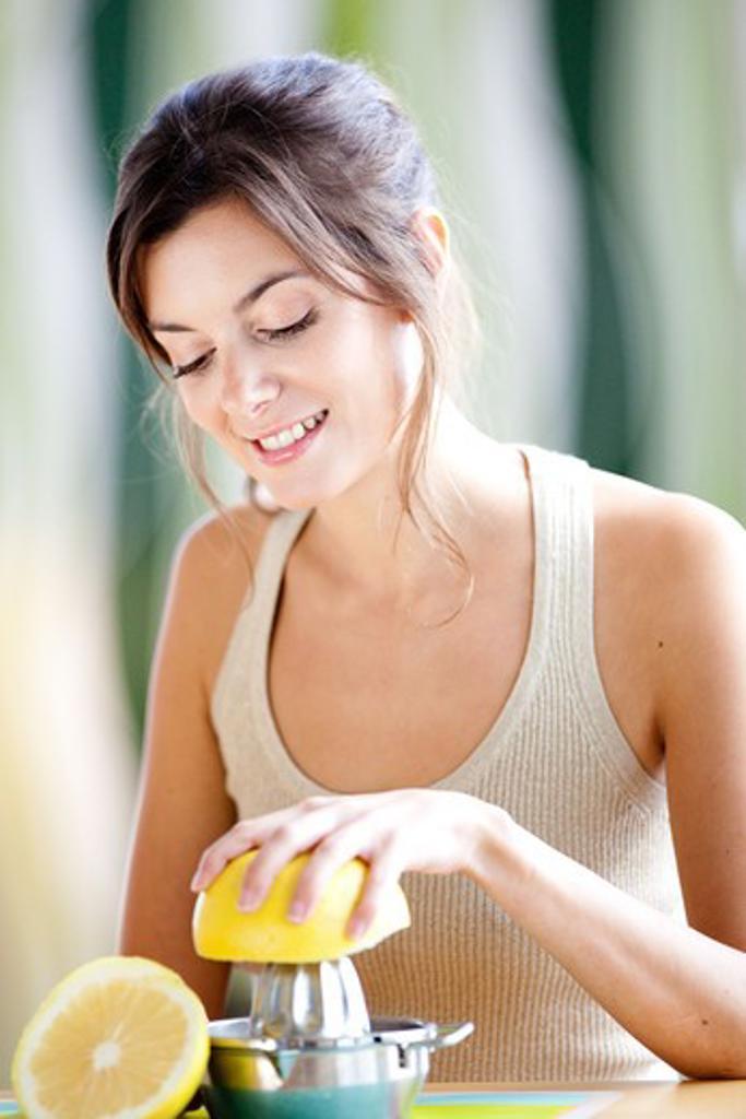 Woman squeezing fresh grapefruit juice. : Stock Photo