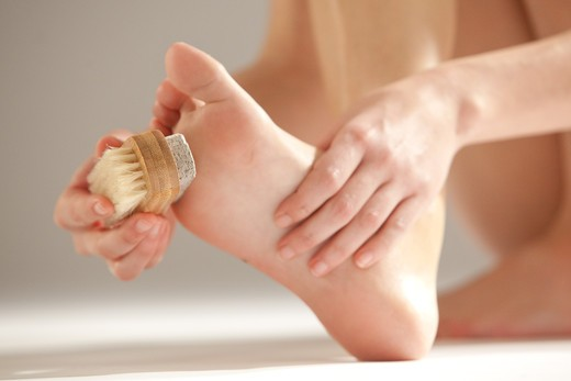 Woman removing hard skin on her foot with a foot file. : Stock Photo