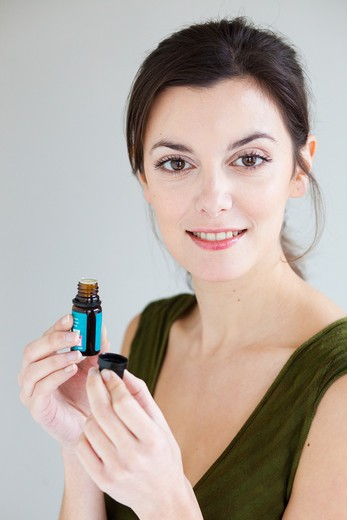Stock Photo: 4269-17107 Woman holding bottle of essential oils.