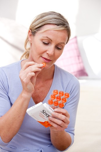 Woman taking lozenge for sorethroat. : Stock Photo