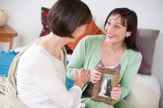 Mother and daughter speaking about an old family picture. : Stock Photo