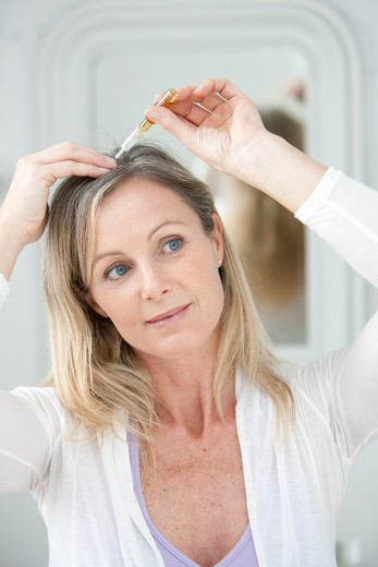 Stock Photo: 4269-17842 Woman applying hair lotion.