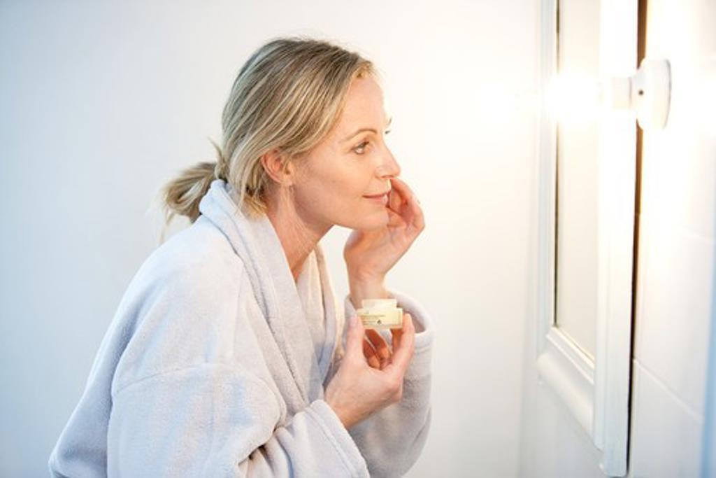 Woman applying moisturizing cream on her face. : Stock Photo