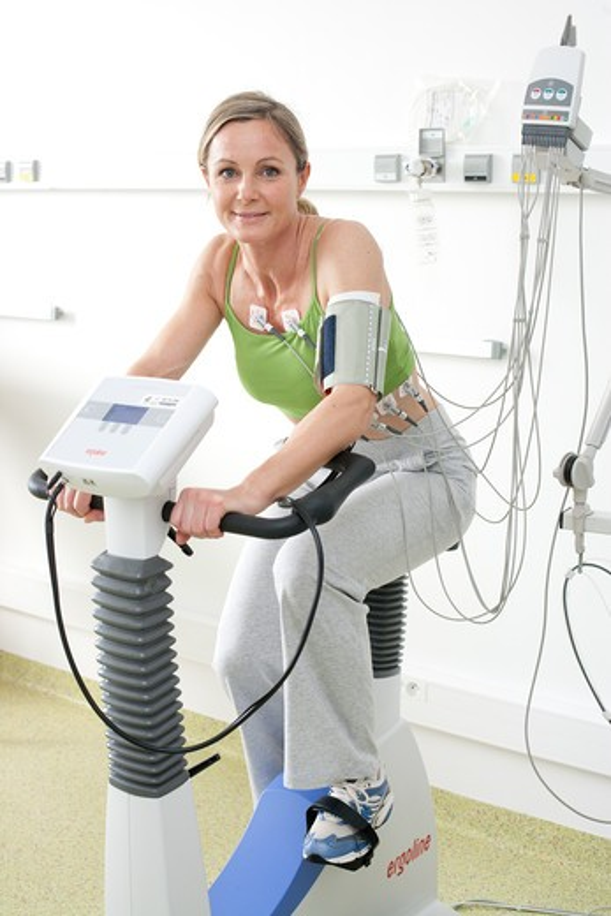 Patient doing monitored heart rehabilitation training exercises on ergometric bicycle. Limoges hospital, France. : Stock Photo