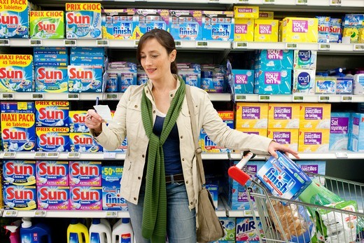 Woman shopping in cleaning products section in supermarket. : Stock Photo