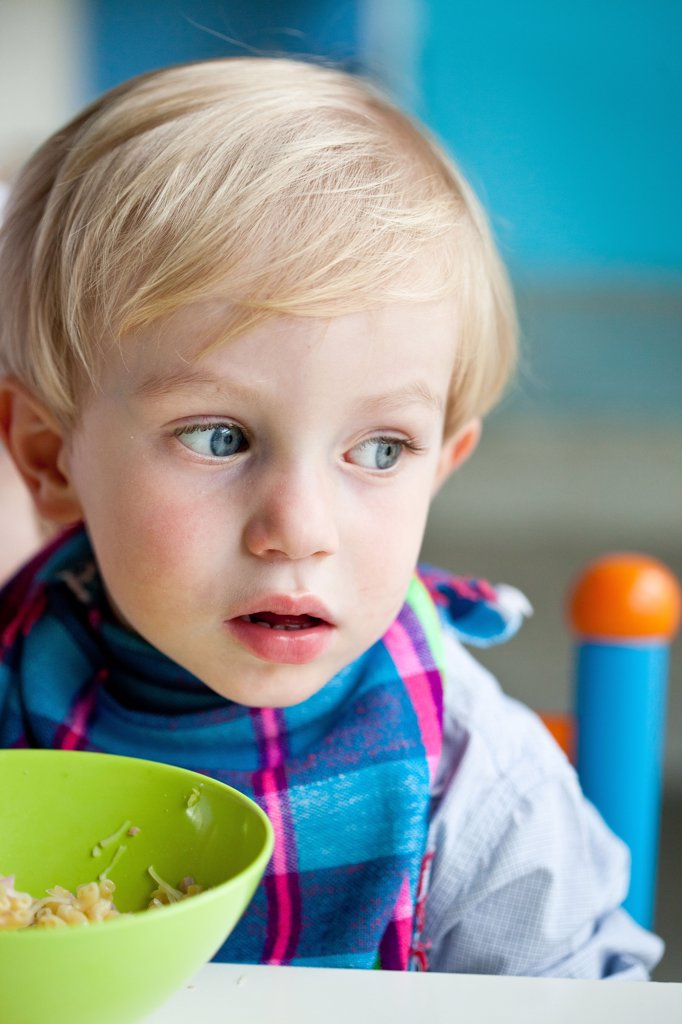 3 years old boy eating pasta. : Stock Photo