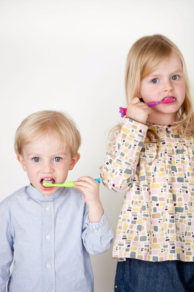 Brother and sister brushing their teeth. : Stock Photo