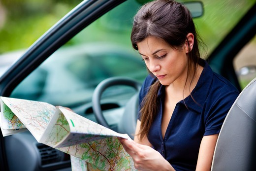 Woman driver reading a road map. : Stock Photo