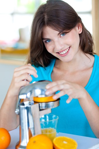 Stock Photo: 4269-19732 Woman squeezing fresh orange juice.