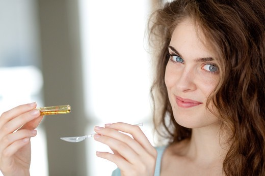 Woman holding glass ampoule of vitamin D. : Stock Photo