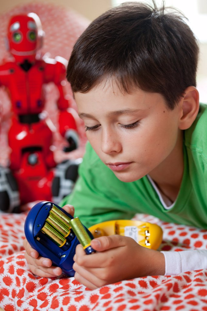 Stock Photo: 4269-20986 Boy using charger for rechargeable batteries.