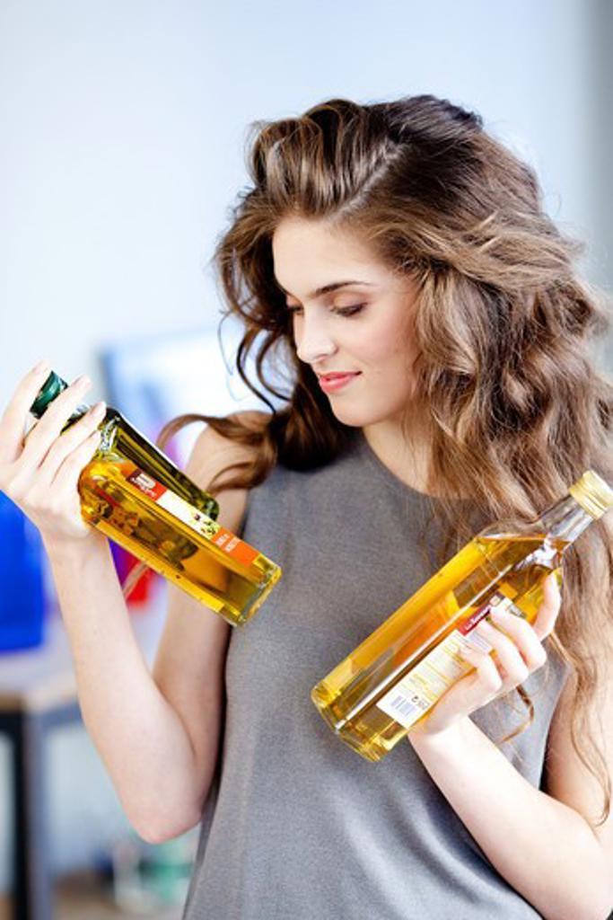 Stock Photo: 4269-21032 Woman holding oil bottles.