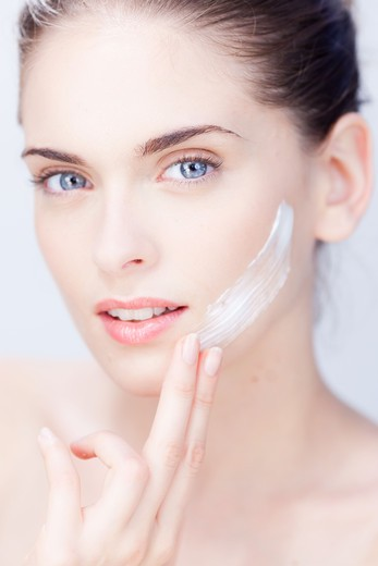 Woman applying moisturizing cream on her face. : Stock Photo