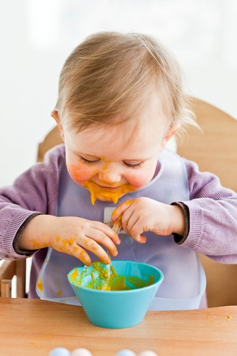 Stock Photo: 4269-23448 13 month old baby girl eating alone. Independence training.