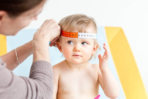 Stock Photo: 4269-24033 Measurement of the circumference of a 14 months old baby's head (cranial perimeter) with a tape measure.