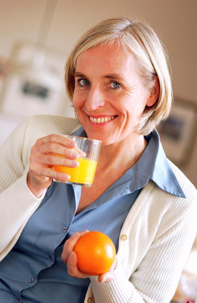 Senior. Woman drinking orange juice. : Stock Photo
