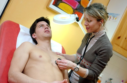 Medical consultation. The doctor examines the chest of a patient with a stethoscope. : Stock Photo