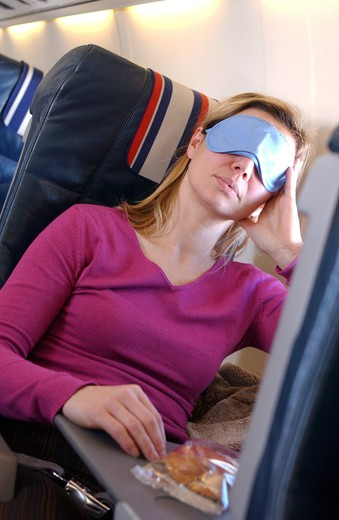 Stock Photo: 4269-26926 Woman. Air travel : woman asleep in a plane with mask over her eyes.
