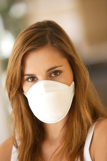 Woman wearing a protective breathing mask FFP2 (in conformity with the standard EN149:2001). It is recommended to wear this mask in case of flu pandemic. : Stock Photo