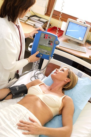 Stock Photo: 4269-2840 A cardiologist checks the blood pressure of a patient during medical consultation at hospital.