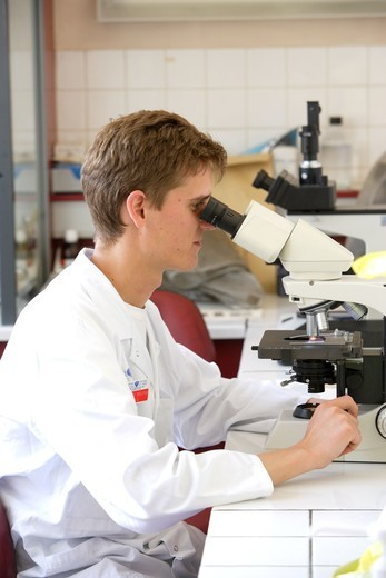 Stock Photo: 4269-2870 A laboratory technician is examining a blood sample (blood smear) on a light microscope, to search for malaria parasite (plasmodium). Laboratory of Parasitology and Mycology, Department of Pr Dupouy-Camet, Cochin Hospital, Paris, France.