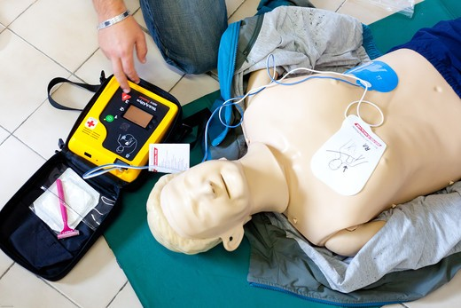 First aid training courses. Portable semi-automatic heart defibrillator used on a mannequin. : Stock Photo