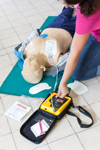 Stock Photo: 4269-29421 First aid training courses. Portable semi-automatic heart defibrillator used on a mannequin.