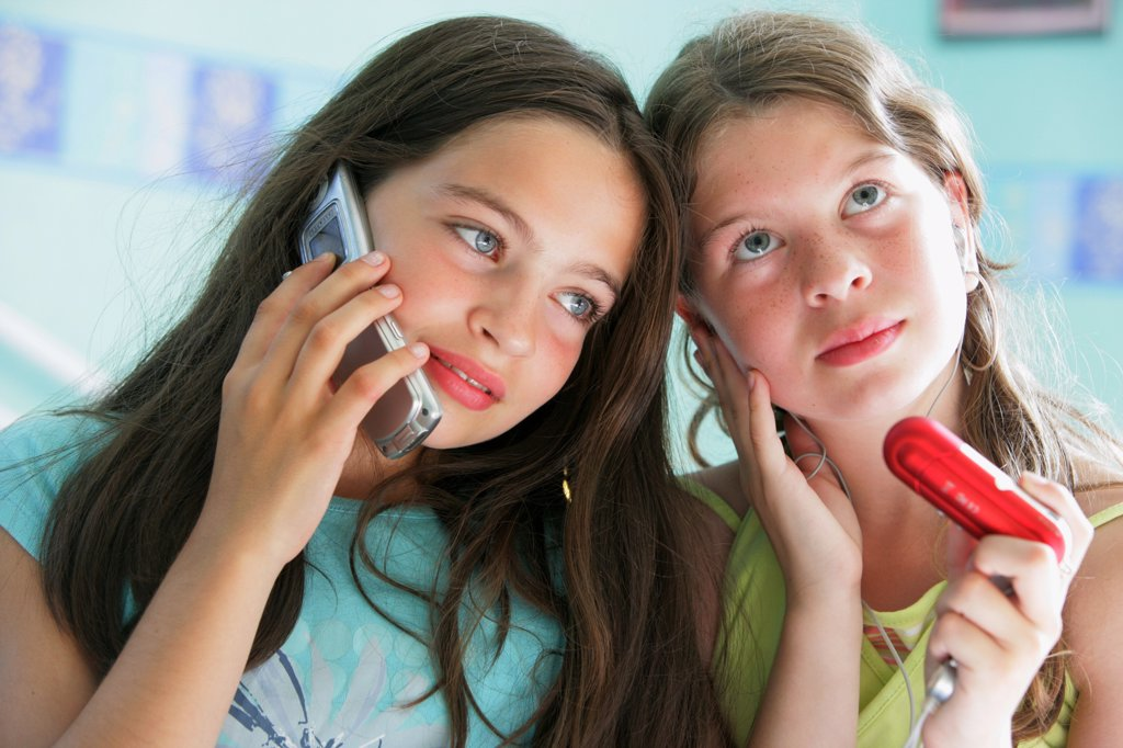 12 years old girl listening to music on mp3 player and her 11 years old sister talking on cell phone. : Stock Photo
