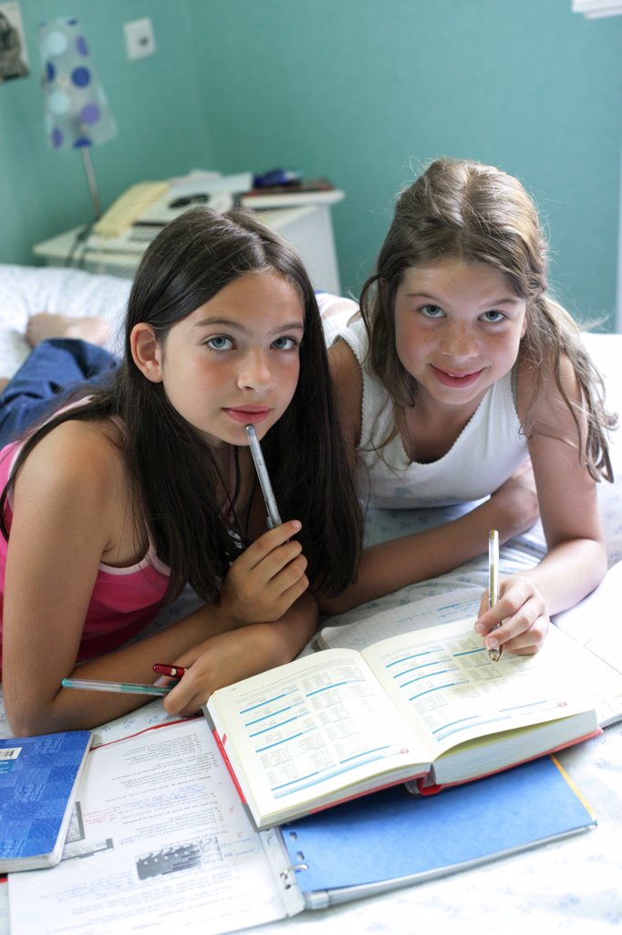 11 and 12 years old sisters doing their homework. : Stock Photo