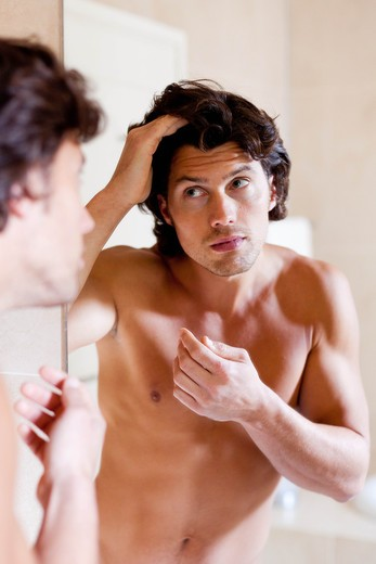 Loss of hair. Man inspecting his hair in a mirror. : Stock Photo