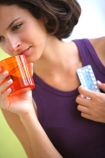 Young woman taking contraceptive pills. : Stock Photo
