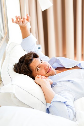 Stock Photo: 4269-31615 Man waking up and stretching in bed.