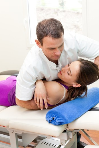 Stock Photo: 4269-32764 Structural osteopathy session on a woman with low back pain.