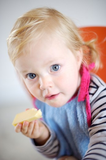 Stock Photo: 4269-3318 18 months old baby girl eating cheese.