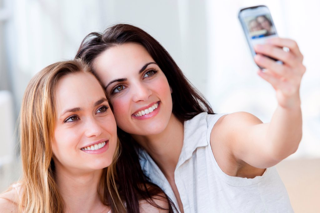 Young women photographing with a Smartphone. : Stock Photo