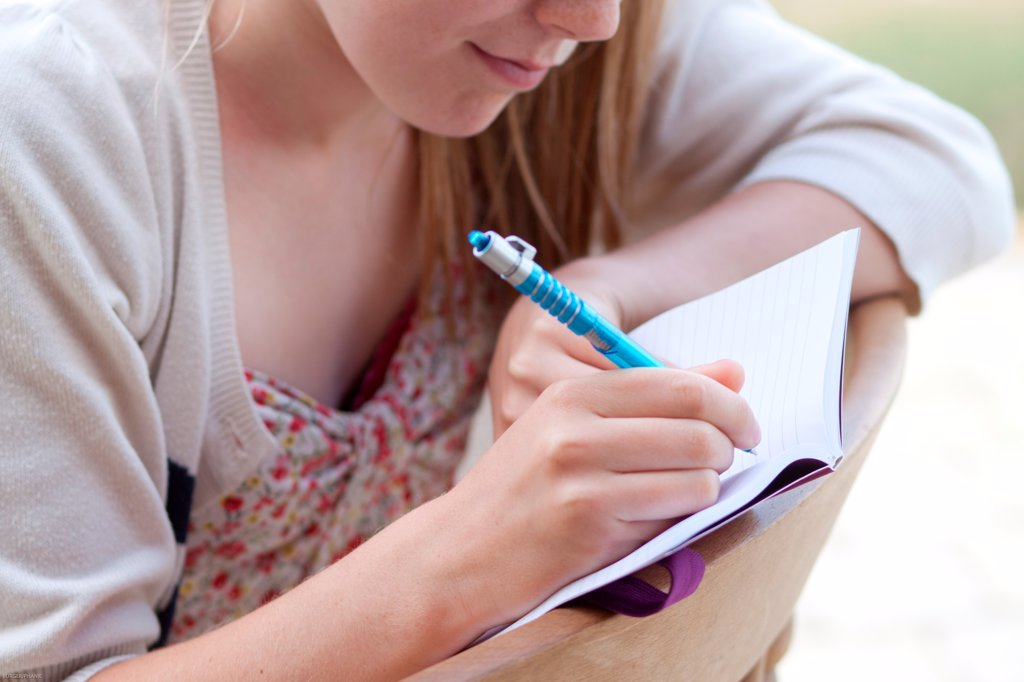 Stock Photo: 4269-34702 Teenage girl writing on her diary.