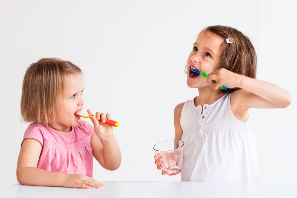 2 and 5 year old girls brushing their teeth : Stock Photo